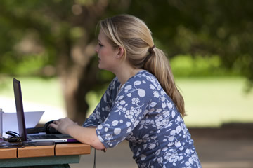 female student studying outside with laptop